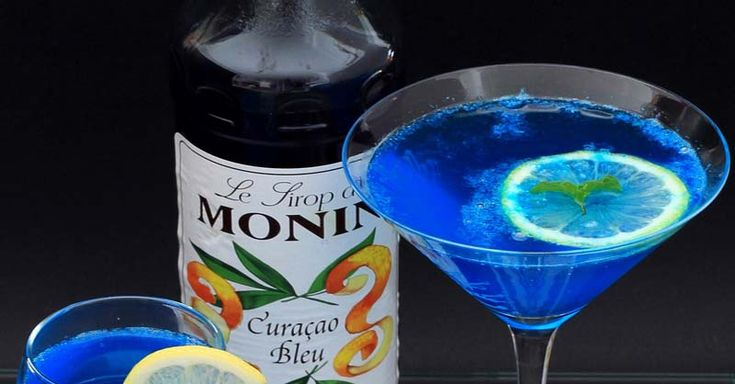 """El cocktail Blue Lagoon fue creado en Gran Bretaña en la década de los 50. Su nombre significa en castellano """"Laguna azul"""", debido al intenso color azul de esta bebida. Otros investigadores plantean que esta bebida proviene de un bar neoyorquino, el Harry's New York Bar."""