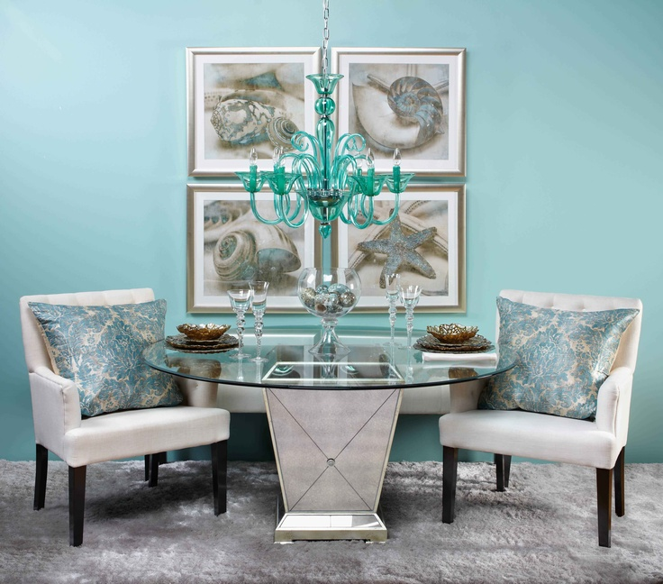 Luxurious dining area with a mirrored table. Also, a glass-topped table helps a smaller room feel more spacious.