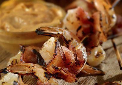 Gegrilde garnalen zijn makkelijk te maken en vormen een geweldige aanvulling voor elke barbecue. Dit recept is veruit mijn favoriet, indien gemarineerd in een heerlijke mix van sjalotten, knoflook, gember, peper, sojasaus en pindaolie. Serveer met rode linzenpuree voor nog meer smaak.