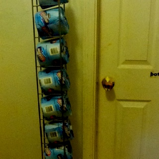 Re-purposed cd rack, thrift store find. Toilet paper roll rack...thinking outside the box. Planning a fabric cover that matches the shower curtain.