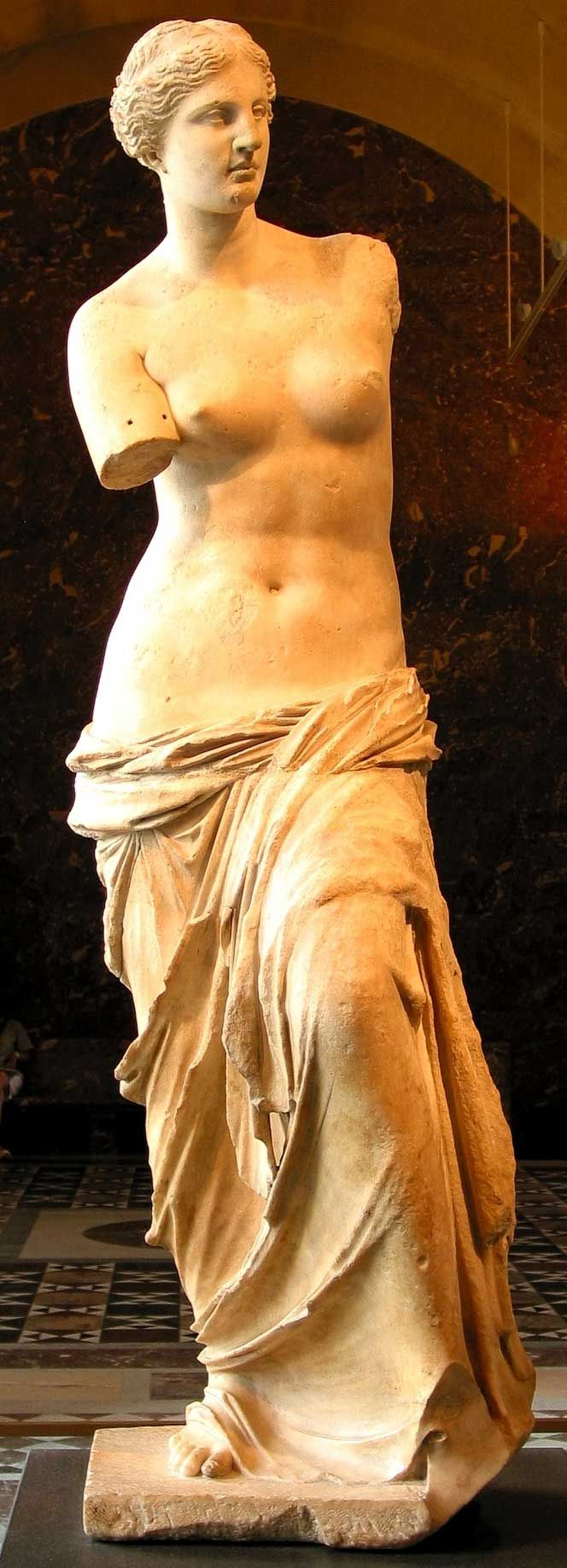 Venus de Milo-Aphrodite of Milos (Greek: Ἀφροδίτη τῆς Μήλου), Louvre Museum, Paris. Ancient Greek statue and one of the most famous works of ancient Greek sculpture. Created between 130 and 100 BC, it is believed to depict Aphrodite the Greek goddess of love and beauty. It is a marble sculpture, slightly larger than life size at 203 cm (6 ft 8 in) high. Its arms and original plinth have been lost. From an inscription that was on its plinth, it is thought to be the work of Alexandros of…