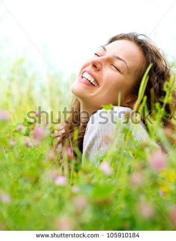 Beautiful Young Woman lying in Meadow of Flowers. Enjoy Nature - stock photo