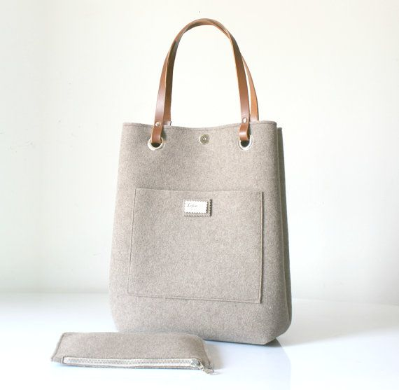 Tote bag - taupe coloured   Felt Tote Bag which is handmade from 3mm Felt and High Quality Italian Leather. The Leather is Vegetable tanned and handcut. The bag, thanks to the metal clip inside, has two different shapes: larger or smaller on the top, suitable for every occasion in your everyday life. Because of its big dimensions, it is a perfect bag for carrying everything: computer, laptop, clothes etc. The 3 mm felt is made of 90% wool and 10% cotton. This kind of felt is softer and…