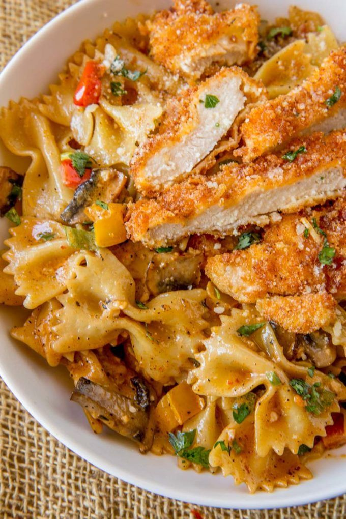Cheesecake Factory Copycat Louisiana Chicken Pasta with Parmesan cheese, mushrooms, bell peppers and onions in a spicy cajun cream sauce.