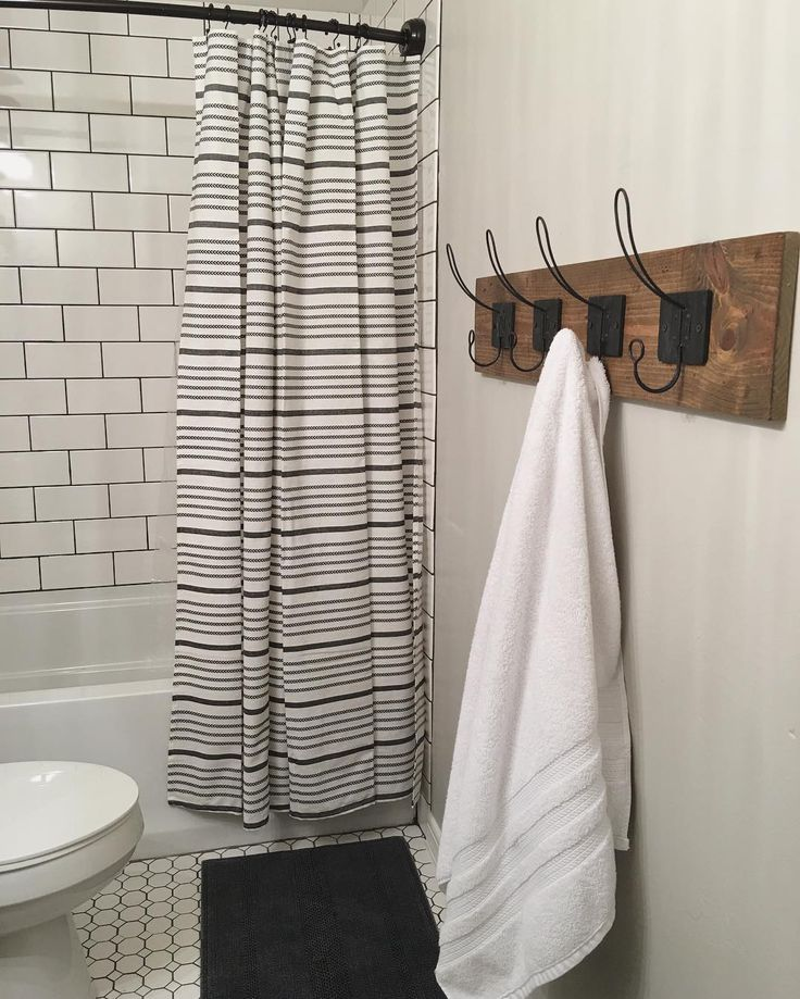 """Ok here's a closer look for those who asked: the shower curtain is from @target. Just search """"ebony shower curtain"""" and it's the first one. It has a little arrow like pattern on the thinner stripes and the white is creamy. It's supposed to be black but paired with indigo, it looks more navy. The fabric is a great quality and feels heavier than most shower curtains. Btw, it's on sale now ;) also, here's a closer look at the towel rack. The hooks from @hobbylobby came with two keyholes on the…"""