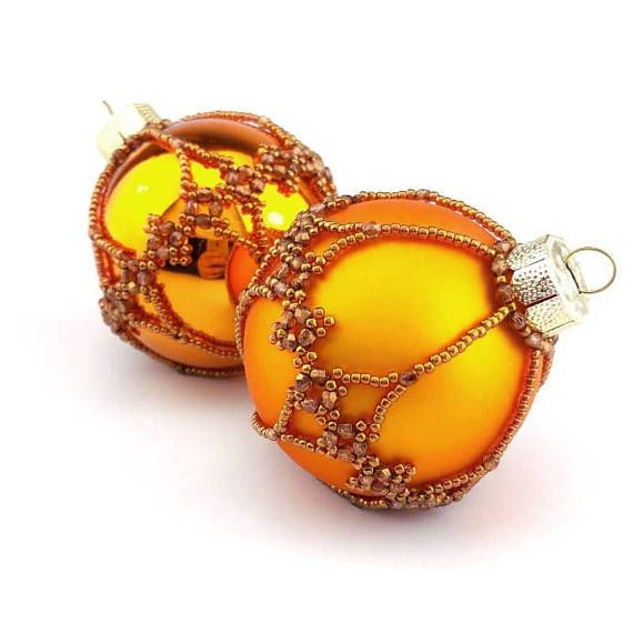 Shiny orange bauble with golden Filigree pattern. (colour number: 114-506) This is an original pattern by Sine Hummel. Our baubles are made from real glass, and will add an elegant air to your tree or decorations. The beads give them a hint of antique or vintage. The baubles are