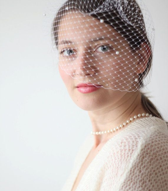 This pearl veil could be a lovely vintage-inspired addition to your bridal outfit. It is attached to a silver tone metal comb for an easy fit.