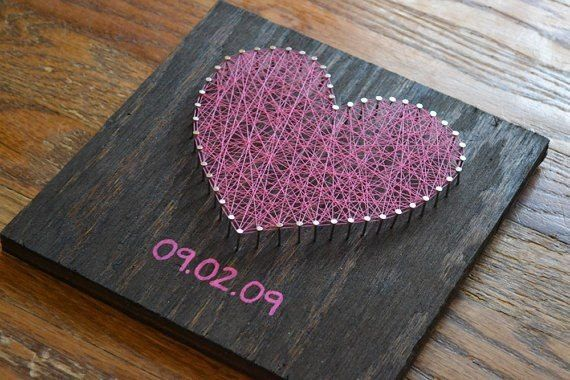 Nail your love down for each other with this DIY craft utilizing nails, yarn, and a wood placque.