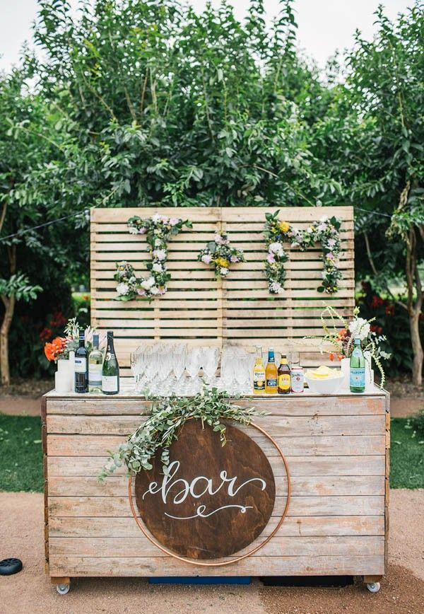 A rustic, hand-crafted drink bar made with wooden palettes and finished off with floral arrangements made in the couple's initials   Image by Hannah Blackmore Photography