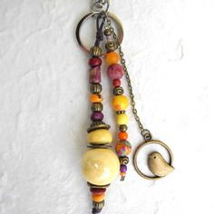 Porte-clés ou bijou de sac, fantaisie, ethnique,  bohème chic, en perles naturelles, jaune orange fuchsia, au petit oiseau suspendu