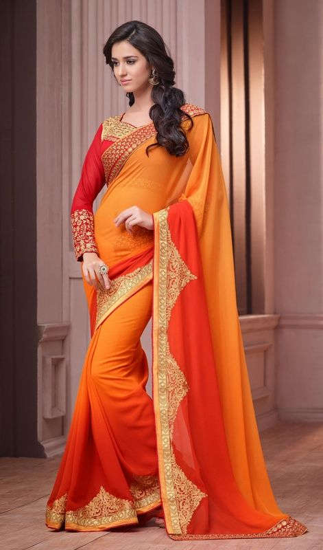 Look trendier than your friends in this tomato and orange color shade georgette sari. The butta, lace, resham and sequins work seems to be chic and perfect for any function. Upon request we can make round front/back neck and short 6 inches sleeves regular saree blouse also. #OrangeSunShineColorOfSaree