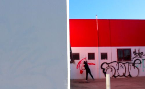 Untitled (clean up after yourself) (2014). Video still- graffitied a building with red paint and then immediately cleaning off the paint.