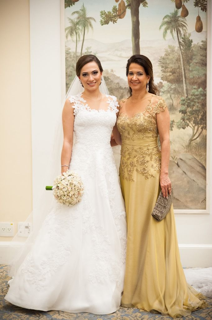 This bride looks lovely in her wedding gown and the #motherofthebride looks great in her #gold colored formal gown. See other #motherofthebridedresses and #bridalgowns that you can have made to order with any custom changes on our site at www.dariuscordell.com