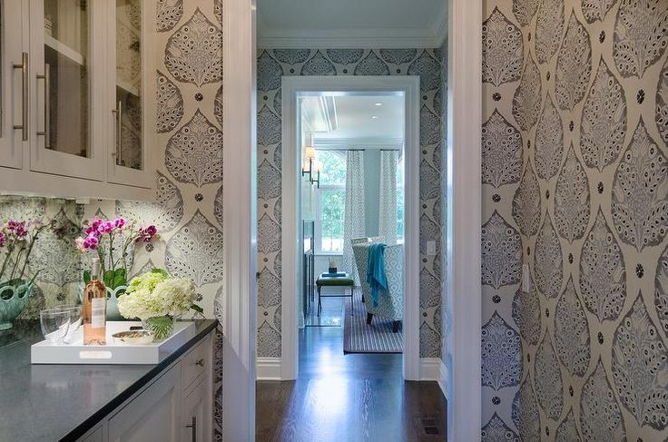 Chic butler's pantry features walls clad in Galbraith & Paul Lotus Wallpaper lined with glass front upper cabinets and white lower cabinets paired with a black quartz countertop and a mirrored backsplash.