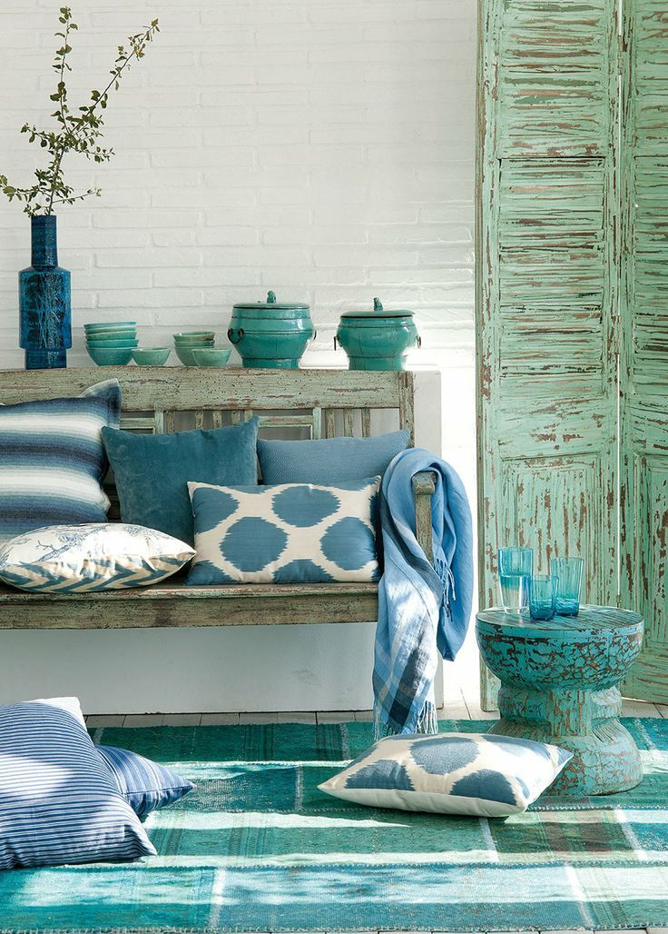 Again, we love the multi-tonal effect of the many hues of cerulean and teal juxtaposed against that striking white wall. And those distressed shutters really tie the look together.