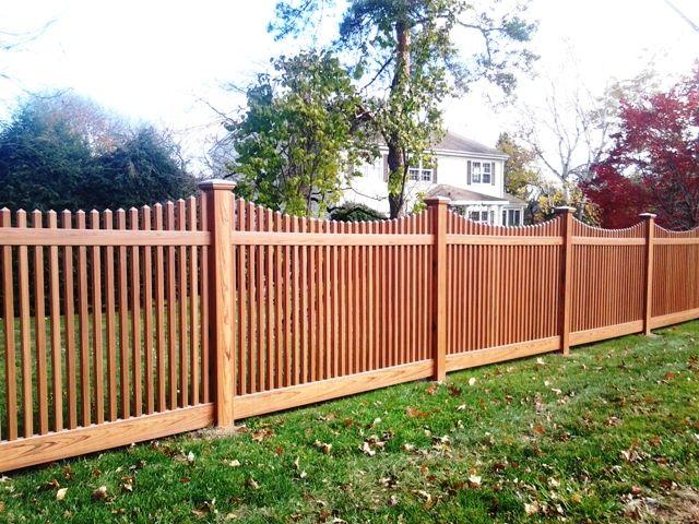 Scalloped woodgrain vinyl picket fence