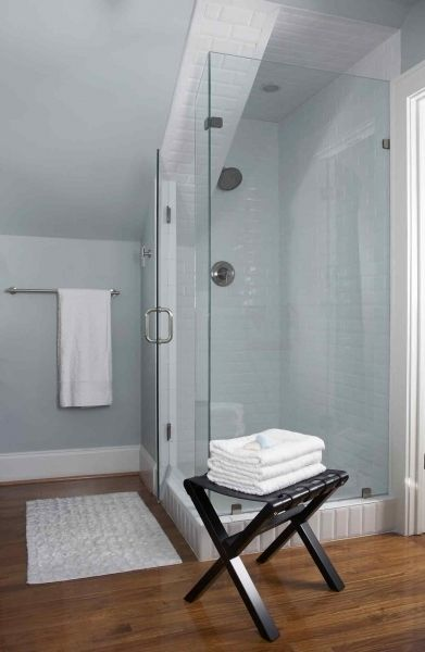 Gorgeous attic bathroom with sloped ceiling, blue walls paint color, frameless glass shower with subway tiles shower surround, black stool and white bath mat.