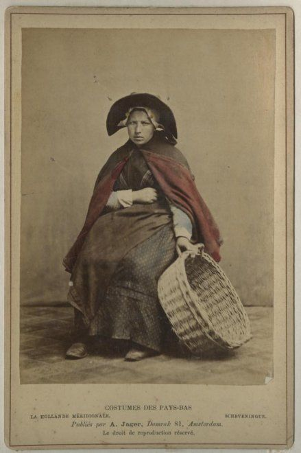 Vrouw in Scheveningse dracht; negotiante (visverkoopster) met vishoed en vismand; zij draagt een katoenen gebloemd jak, een donkergekleurde katoenen rok, omgeslagen schort, een heel smal doekje, een schoudermantel met waarschijnlijk rode baai gevoerd, muts met klappen, ijzer met stukken, haar in een toer. ca 1890 A. Jager, Amsterdam #ZuidHolland #Scheveningen