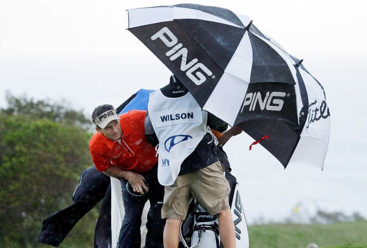 Mark Wilson peers out from under an umbrella as he waits for a rain squall to ease up before teeing off on the 10th hole during the first round at the Tournament of Champions PGA golf tournament, Monday, Jan. 7, 2013, in Kapalua, Hawaii.