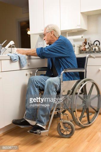 Stock-Foto : Senior man in wheelchair washing dishes