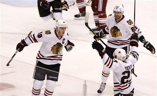 Chicago Blackhawks' Jonathan Toews (19) celebrates his game-winning goal against the Phoenix Coyotes with teammates Viktor Stalberg (25), of Sweden, and Johnny Oduya (27) during overtime in Game 5 of an NHL hockey Stanley Cup first-round playoff series Saturday, April 21, 2012, in Glendale, Ariz. The Blackhawks defeated the Coyotes 2-1.(AP Photo/Ross D. Franklin)