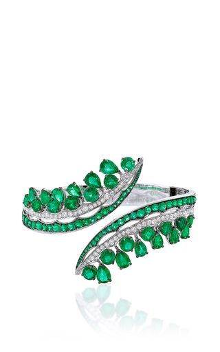 This scintillating bangle, intricately embellished with round brilliant diamonds, features lavish Gemfield sourced Zambian emeralds cascading throughout.