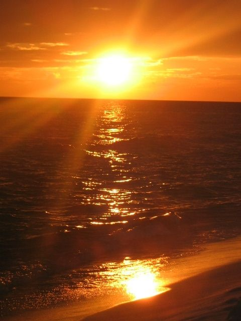 sunset on the water and sand by in Panama City Beach Florida