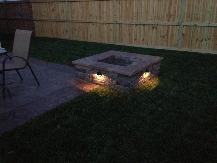 Stamped concrete patio with fire pit on the corner.  Embedded outdoor lights on the pit.