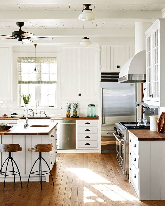Warm Wood Floors And Counters With White Cabinets In Traditional Farm House Style Kitchen Design