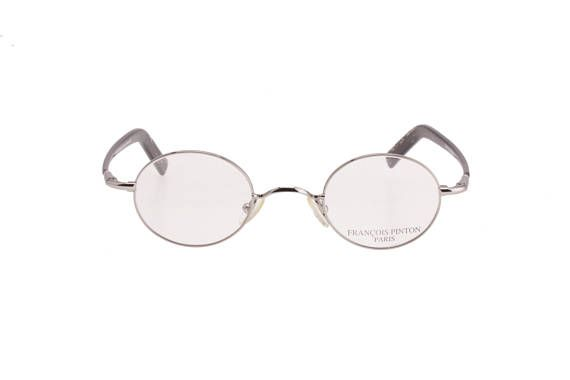 A beautiful classy François Pinton eyeglasses frame made in France in the 1990s. Silver metal high quality oval frame, sporting a nice large nose bridge, as well as an interesting large temples design, made with speckled black and grey cello. The article is new from deadstock,