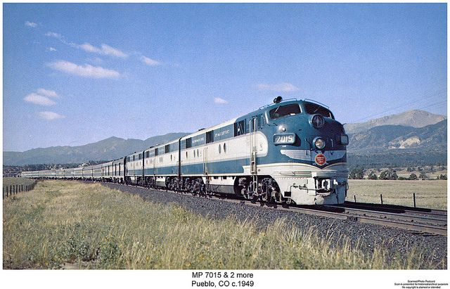 Westbound [Colorado] Eagle speeding toward Denver on Atchison, Topeka & Santa Fe iron north of Pueblo. Pike's Peak's 14,110 ft. suffit, about 40 miles distant, can be seen to the right.  ...E7-model locomotives, like the 7015,shown, of two and three units, pulled the enlarged formation.. There are a baggage-express car, RPO car, 4 coaches, Planetarium [dome] coach, diner, & 4 sleeping cars, some of which were heavy-weights adapted for high-speed service. Missouri Pacific Railroad Company.