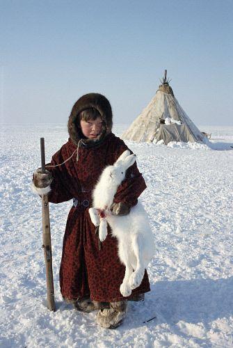 Shurik, a young Tundra Nenets boy poses with an Arctic Hare he has shot. Gydan Peninsula, Western Siberia, Russia.