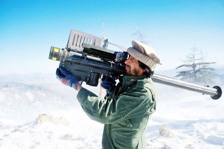 "In Afghanistan, 1988, a Mujahideen fighter aims an FIM-92 Stinger missile at passing aircraft, armed through the CIA's ""Operation Cyclone"" program."