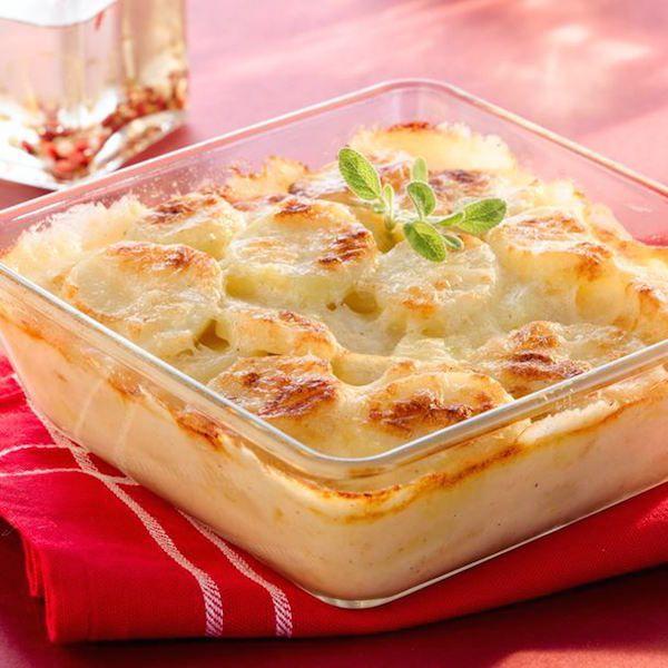 Epluchez et lavez les pommes de terre, puis coupez-les en tranches de 5 mm d'épaisseur. Frottez un plat à gratin avec la gousse d'ail et beurrez-le légèrement. Tapissez le fond du plat avec du poivre et un peu de sel...