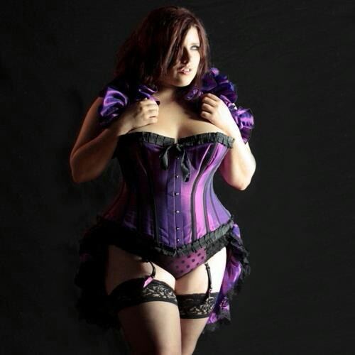 Beautiful bbw in a violet corset with black trim, and black stockings