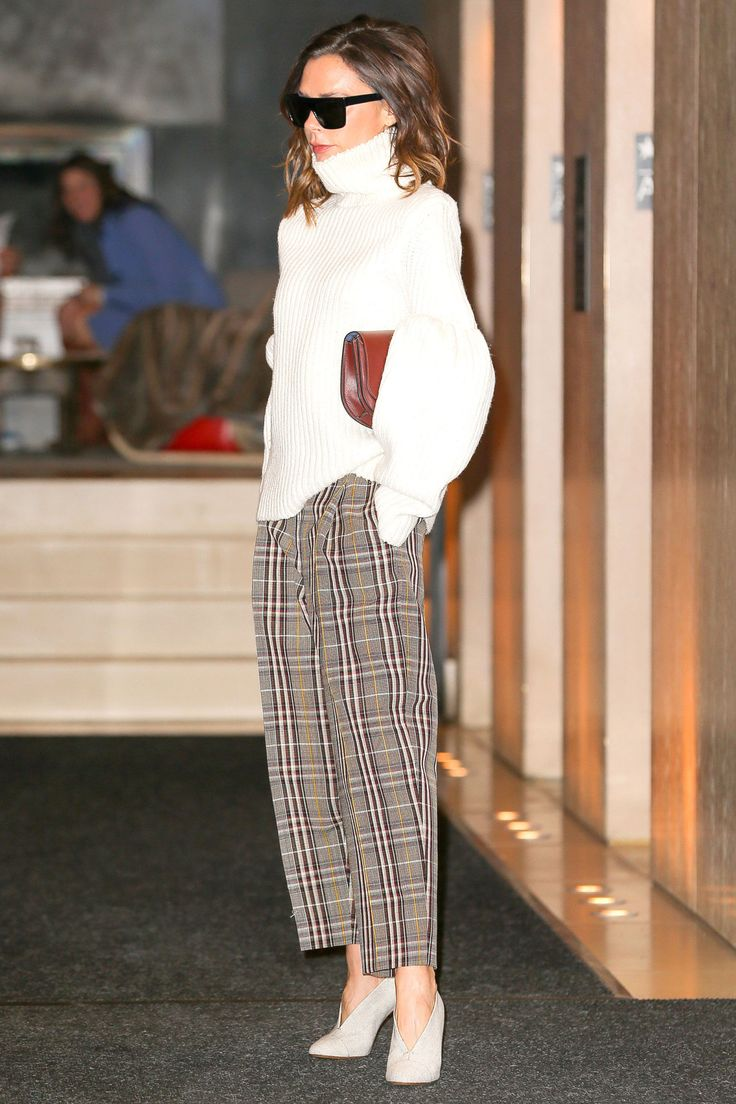 Victoria Beckham in plaid pants with a cream knit turtleneck.