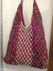Recycled Silk and Hemp Macrame Purse Beautiful recycled sari silk gives this bag it's jewel tones, hemp macrame in the center make it interesting! Lined in cotton with a toggle closure at the top. Made in Nepal.