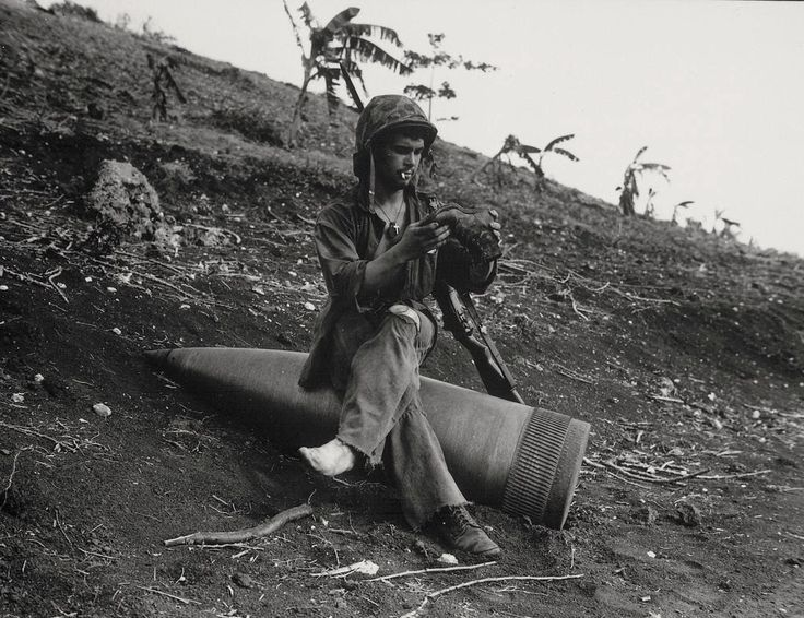 US Marine on an unexploded 16-inch shell fired from a battleship in support of the Battle of Saipan, 1944