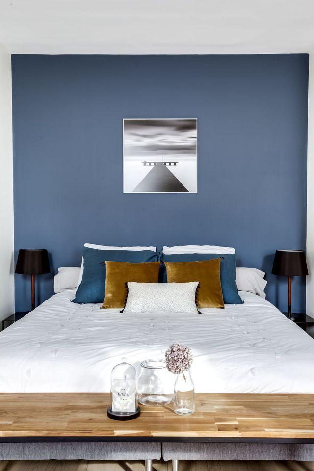 Avec son mur bleu profond, la chambre impose son caractère