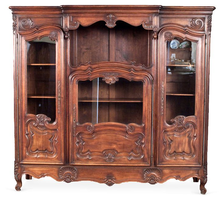 A majestic three-door Louis XV-style bookcase from the 1920s, purchased in the city of Lyon. The doors have raised panels and carved motifs of shells, scrolls and flowers. The patina of the dark...