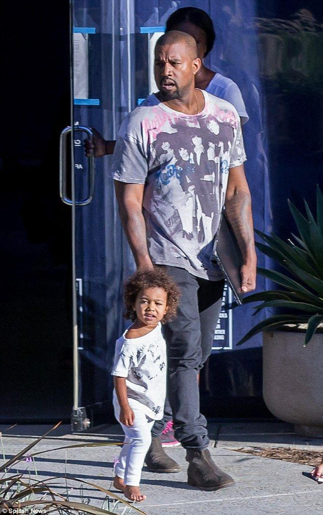 Curly cutie: Rapper Kanye West holds daughter North West's hand as they exit a building in Calabasas on Friday