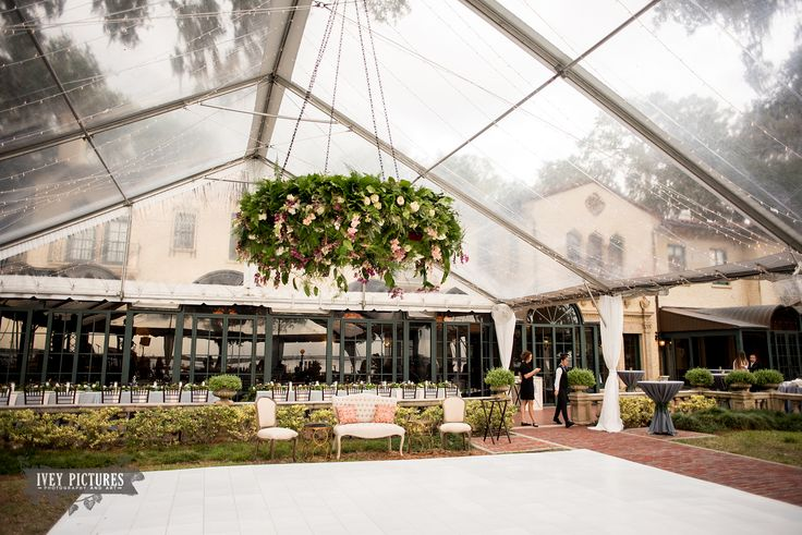 under a clear tent, a majestic floral wreath of eucalyptus/fern/plumosa filled with quicksand rose, white majolik spray rose, burgundy carnation, mauve carnation, vendela rose, peach stock, bleeding heart vines & purple plum branches is hung over the white dance floor like a chandelier .