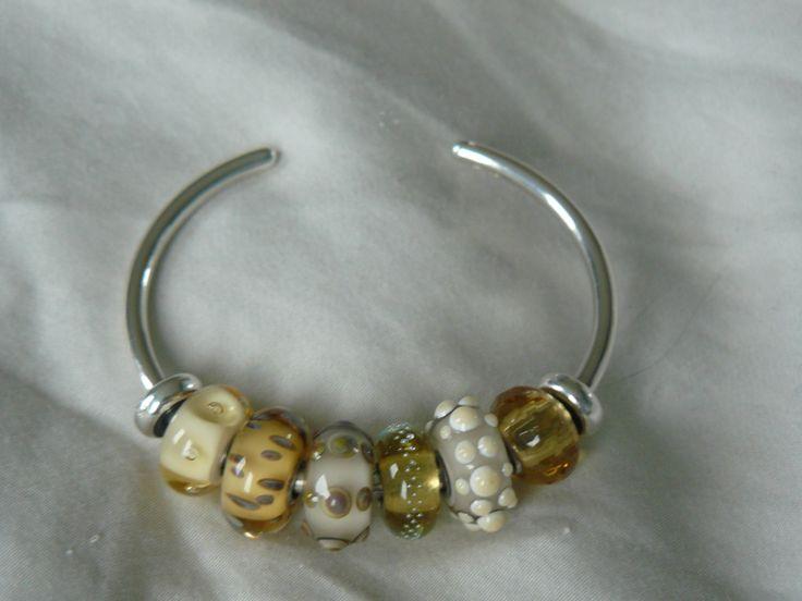 Mooi Goud/geel: Beige luchtbellen, verwaaide zaden, zee-egel, beige zilverspoor, schelp, gele prisma van Trollbeads