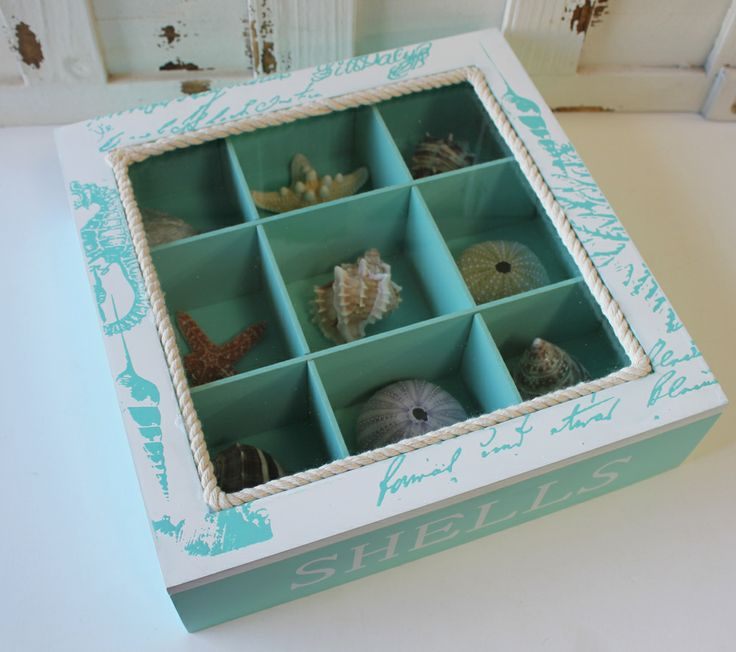 """Sea Shell Display Box - Coastal Decor What a fun and clever way to display shells that you've either collected at the beach yourself on a special vacation or honeymoon, or that you've chosen for our vast selection. Either way, this shell display box makes an excellent conversation piece for a coffee or console table at your beach and coastal themed home. The display box measures 10"""" x 10"""" x 2 3/4"""" and holds 9 shells, starfish or sea urchins."""