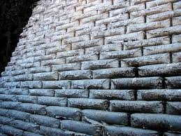 a retaining wall made of unopened stacks of concrete bags