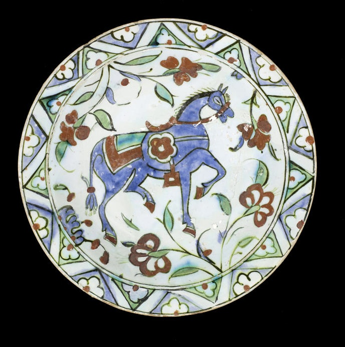 An Iznik pottery Dish   Turkey, 17th Century  of shallow rounded form, underglaze decorated in cobalt blue, green and raised red with black outline depicting a trotting horse surrounded by flowerheads, the rim with a band of interlocking triangles containing trefoil motifs   26 cm. diam.