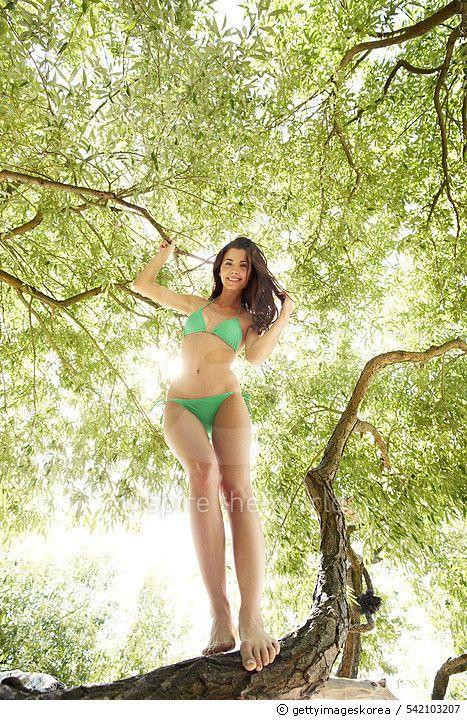 Germany, Hamburg, Young brunette woman in bikini standing on treetop, portrait - gettyimageskorea