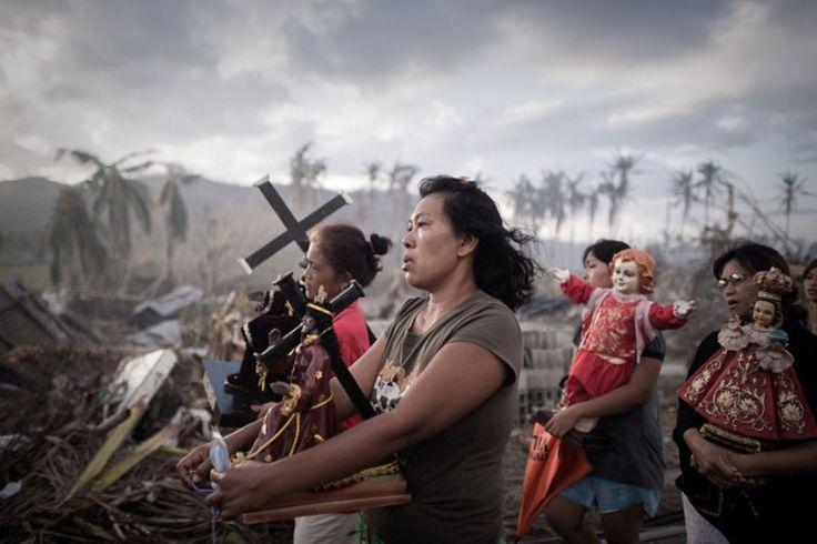 """Foto de Philippe Lopez, Tolosa, Leyte, Filipinas. 18 de noviembre, 2013. """"Noviembre es un mes de tormentas en Filipinas. Las nubes se agolparon en la puesta de sol mientras que a lo largo de la carretera los residentes encendían fuego para quemar los escombros provocados por el tifón. El paisaje devastado adquirió una extraña belleza y un grupo de mujeres y niños aparecieron en el camino""""."""