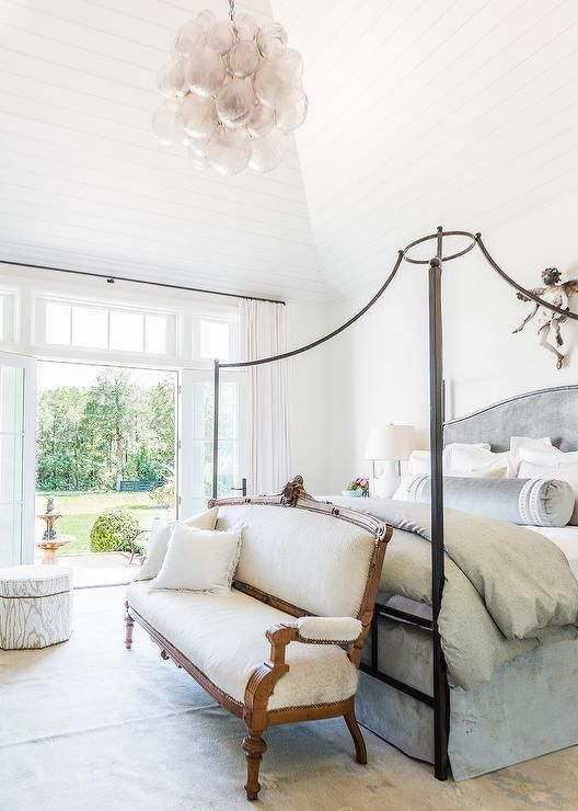 Symphony Showhouse - Beautiful bedroom boasts a paneled vaulted ceiling over an iron canopy bed fitted with a gray velvet headboard with matching bedskirt, gray bolster pillow and a light gray linen duvet alongside a French settee placed at the foot of the bed illuminated by an Oly Studio Muriel Chandelier.
