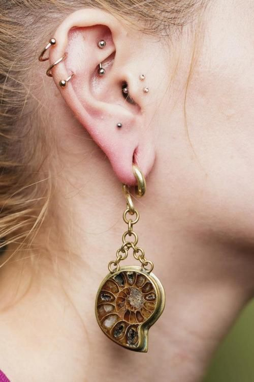 """""""Jimmy Buddha ammonite and brass ear weights in Anna's ears."""""""